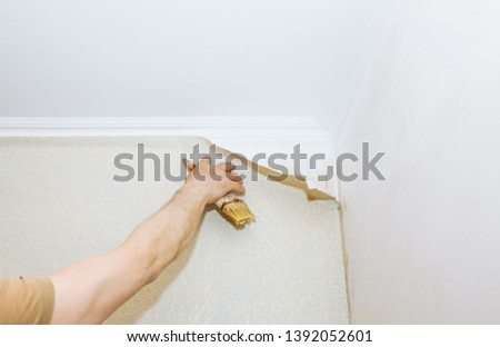 Man is putting glue on the wall with brush. Wallpaper hanging. Maintenance repair works renovation in the flat. Restoration indoors. #1392052601
