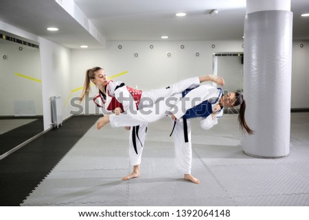 Two girls celebrating sports and demonstrating martial art of taekwondo, concept of hard training #1392064148