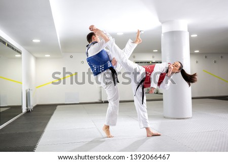 Exchange of high kicks during training of taekwondo between two fighters #1392066467
