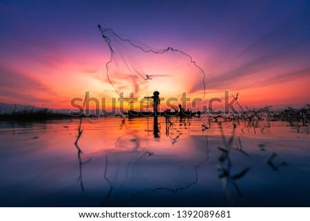 Silhouette of Myanmar fisherman on wooden boat ,Myanmar fisherman in action catching freshwater fish in nature river, Myanmar traditional fishermen at the sunset near Inle lake,Myanmar #1392089681