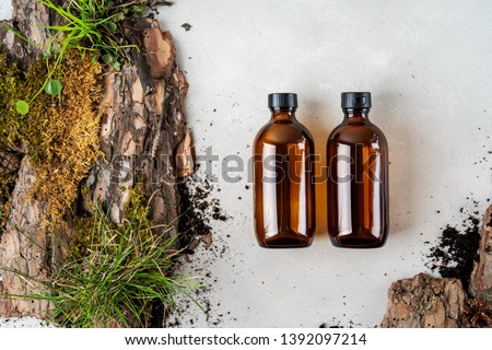 Two brown glass Mock up bottles of shampoo and conditioner of body care cosmetics over Natural background of real tree bark, tiny mosses and grass organic for cosmetic products with copy space.  Royalty-Free Stock Photo #1392097214