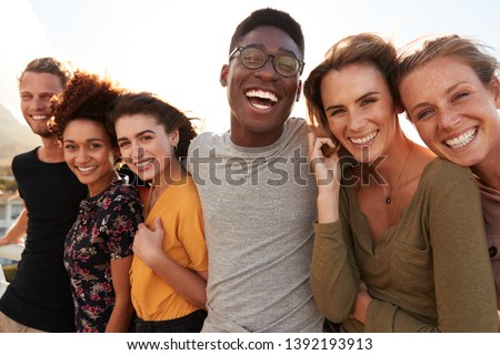 Portrait Of Smiling Young Friends Walking Outdoors Together Royalty-Free Stock Photo #1392193913