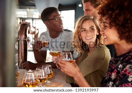 Group Of Friends Beer Tasting Sitting At Bar #1392193997