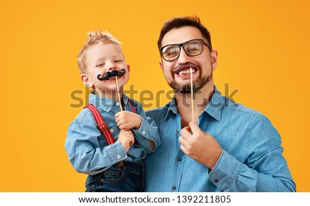 happy father's day! funny dad and son with mustache fooling around on colored yellow background #1392211805