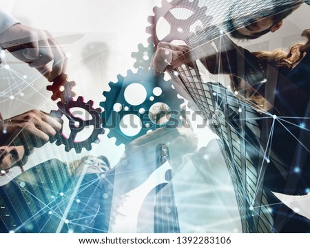 Business team connect pieces of gears. Teamwork, partnership and integration concept. double exposure with network effects #1392283106