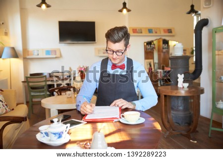 Portrait shot of small business owner young man sitting at desk and doing some paperwork in his cafe. Small business. #1392289223