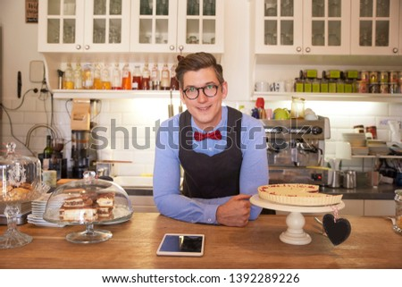 Portrait of confident young man standing in his coffee shop behind the counter and waiting for guest. Small business. #1392289226