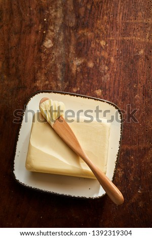 Ceramic butter dish with pat of farm fresh butter and wooden spreader or knife over a rustic old wooden table with copy space #1392319304
