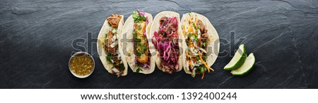 four mexican street tacos with fish barbacoa and carnitas shot in panoramic composition