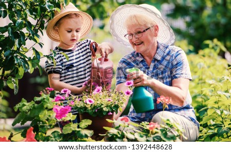 Gardening with kids. Grandmother and her grandchild enjoying in the garden with flowers. Hobbies and leisure, lifestyle, family life #1392448628