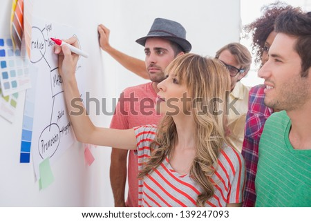 Creative team watching coworker add to flowchart on whiteboard with colour samples #139247093