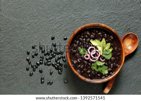 black bean soup or stew. Latin American or Mexican cuisine. stewed black beans served with avocado and red onion and cilantro. place for text. top view. #1392571541
