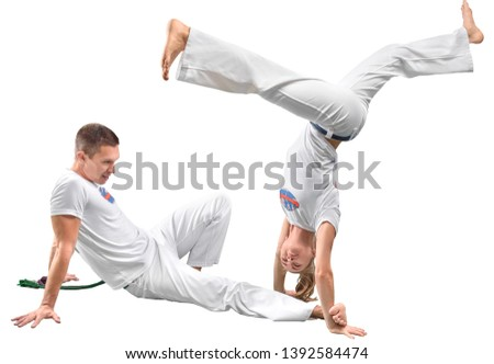 Man and woman does the fighting element of capoeira. A couple of fighters train capoeira isolated on white background - concept about people, lifestyle and sport. #1392584474