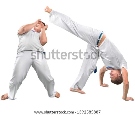 Two men do the fighting element of capoeira. A couple of fighters train capoeira isolated on white background - concept about people, lifestyle and sport.  #1392585887