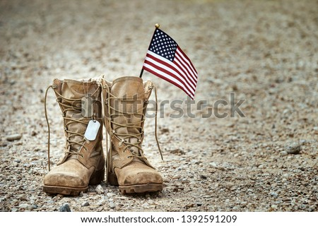 Old military combat boots with dog tags and a small American flag. Rocky gravel background with copy space. Memorial Day, Veterans day, sacrifice concept. Royalty-Free Stock Photo #1392591209