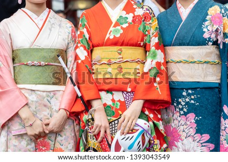 "Young girl wearing Japanese kimono standing in front of Sensoji Temple in Tokyo, Japan. Kimono is a Japanese traditional garment. The word ""kimono"", which actually means a ""thing to wear""  #1393043549"