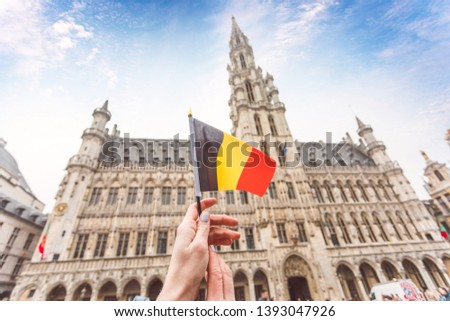 Woman tourist holds in her hand a flag of Belgium against the background of the Grand-Place Square in Brussels, Belgium. Traveling in Belgium, the main attraction of Brussels, the Grand Market Square #1393047926