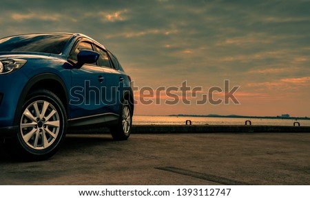 Blue compact SUV car with sport and modern design parked on concrete road by the sea at sunset in the evening. Hybrid and electric car technology concept. Car parking space. Automotive industry.  #1393112747