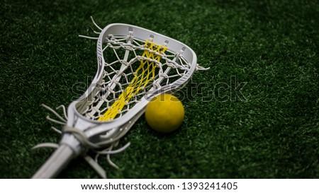 Women's lacrosse stick next to yellow lacrosse balls.