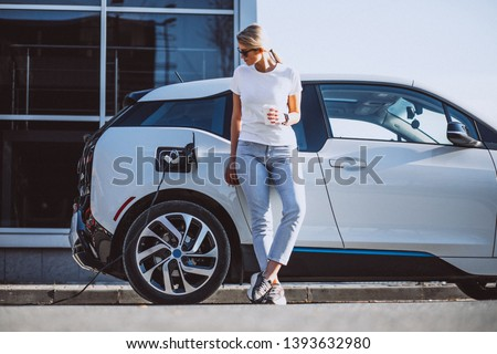 Woman charging electro car at the electric gas station #1393632980
