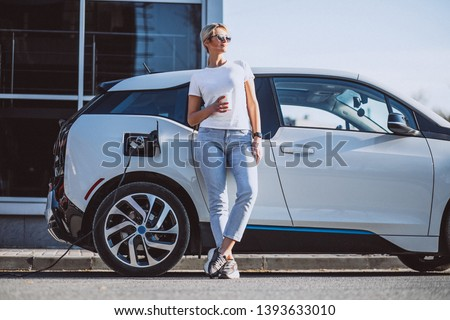 Woman charging electro car at the electric gas station #1393633010