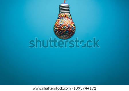 Creative lightbulb filled with multi colored ball on a BLUE background behind. Best idea concept.