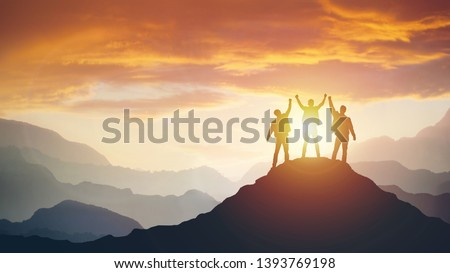 Group of peoples on mountains top in winner pose. Leadership Concept Royalty-Free Stock Photo #1393769198