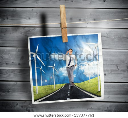 Photo of businessman running on a road with wind turbines hung on a line with a peg and wooden board on the background #139377761