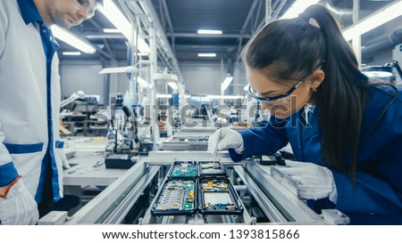 Shot of an Electronics Factory Workers Assembling Circuit Boards by Hand While it Stands on the Assembly Line. High Tech Factory Facility. #1393815866