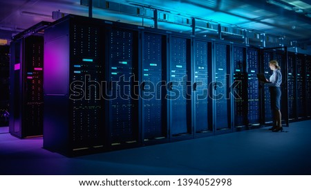 In Data Center: IT Technician Running Maintenance Programme on Laptop, Controls Operational Server Rack Optimal Functioning. Modern High-Tech Telecommunications Operational Data Center in Neon Lights. #1394052998