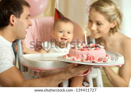 one-year-old little girl with daddy and mammy solemnize birthday, happy laughter, horizontal photo