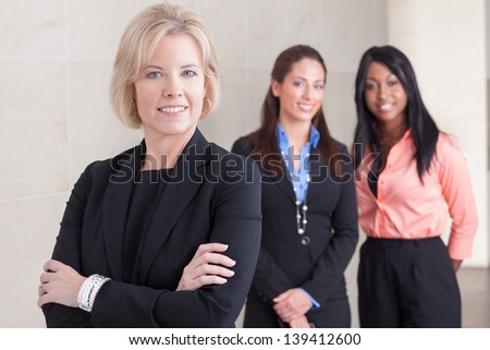 Three business women of varying ethnicities in suits, standing together, smiling and looking at camera, in office #139412600
