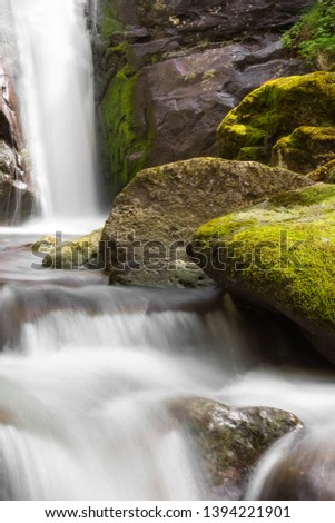 Unique, close up view of a scenic waterfall during spring streaming down the red, wet cliff with vibrant green moss #1394221901