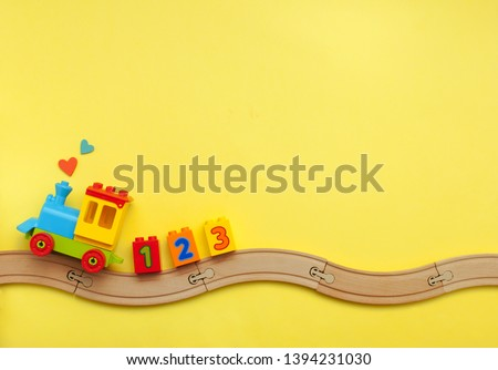 Toys background with copy space. Kids toy train with numbers on toy wooden railway on yellow background with blank space for text. Top view, flat lay. #1394231030