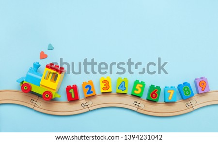 Toys background with copy space. Kids toy train with numbers on toy wooden railway on light blue background with blank space for text. Top view, flat lay. #1394231042