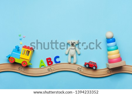 Toys background with copy space. Kids toys train, ABC letters, bear, car and pyramid on toy wooden railway on blue background with blank space for text. Top view, flat lay. #1394233352