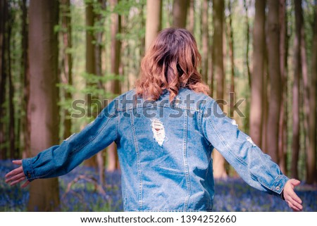 Back view of a young girl wearing denim jacket and the sun lighting up the curls in her hair, enjoying her walk in a bluebell forest. Shinrin yoku concept. Wild and free. Nature love. Royalty-Free Stock Photo #1394252660
