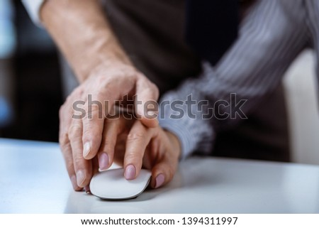 Computer mouse. Inappropriate strong man covering hand of his female workmate and actively seducing her #1394311997