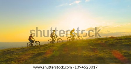AERIAL LENS FLARE COPY SPACE SILHOUETTE: Fit tourists riding electric bicycles along a grassy path on a beautiful sunny spring day. Cinematic shot of three friends enjoying a scenic mountain bike ride Royalty-Free Stock Photo #1394523017