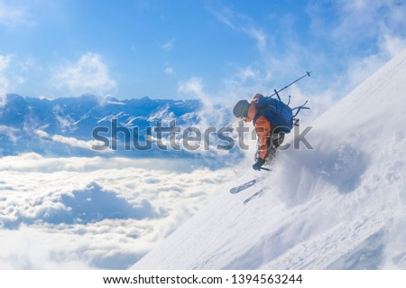 Freeskier on steep slope in backcountry over the clouds at the Nordkette ski resort high over Innsbruck in Tirol #1394563244
