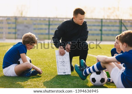 Football coach coaching children. Soccer football training session for children. Young coach teaching kids on football field. Football tactic education. Coach explains the strategy of the game #1394636945