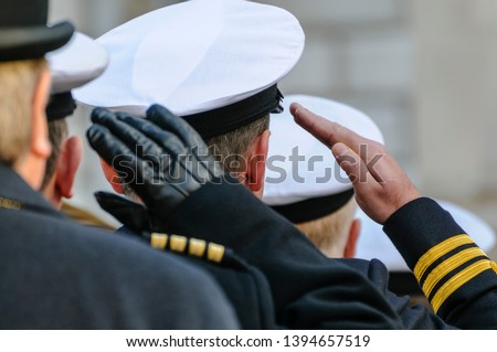 Royal Navy officers salute during Remembrance Day commemorations. Royalty-Free Stock Photo #1394657519