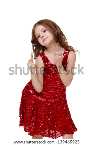 Charming little girl in a shiny red dress holding a makeup brush #139465925