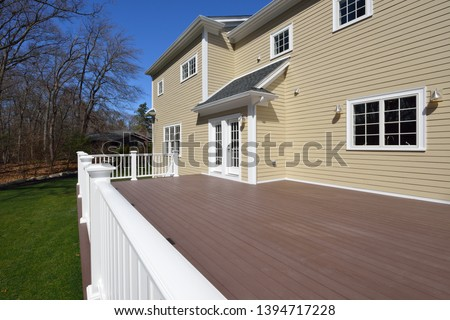 Composite deck in house backyard. Brown boards, white railing posts and veranda. Large, spacious, new construction. #1394717228