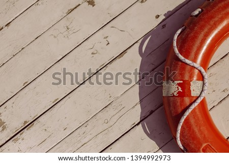 orange lifebuoy on wooden background. Life buoy hanging on wooden wall for emergency response when people sinking to water almost place near pool and beach. vintage photo processing