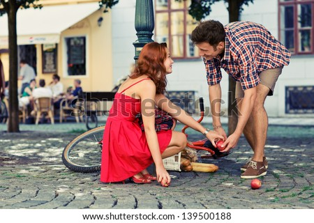 man fell down from the bicycle and woman help him to collect products Royalty-Free Stock Photo #139500188