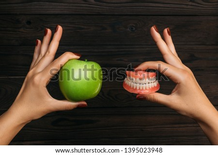 False teeth denture against green granny smith apple. Dental prosthesis care. Denture and Apple in the hands of a doctor. Dental care. Beautiful tooth. Prosthetics. False teeth #1395023948