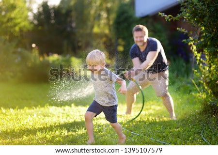 Funny little boy with his father playing with garden hose in sunny backyard. Preschooler child having fun with spray of water. Summer outdoors activity for kids. #1395107579