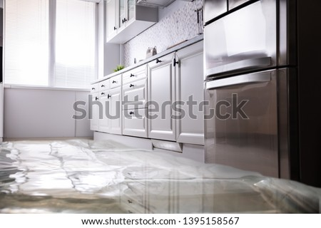 Close-up Of Flooded Floor In Kitchen From Water Leak Royalty-Free Stock Photo #1395158567