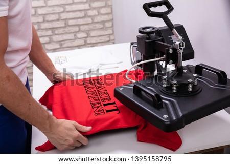 Man printing on t shirt in workshop #1395158795